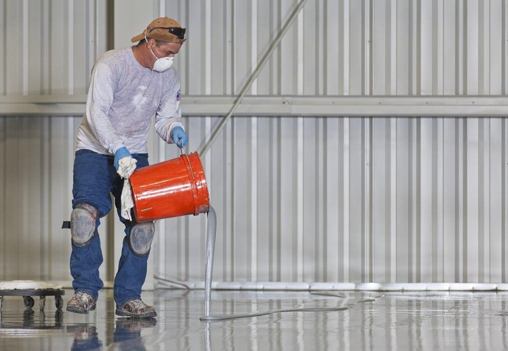 man applying epoxy on flooring