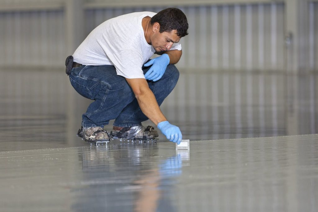 man installing epoxy on the floor