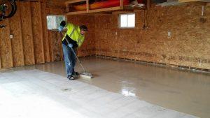 man applying thin epoxy coating on a garage flooring